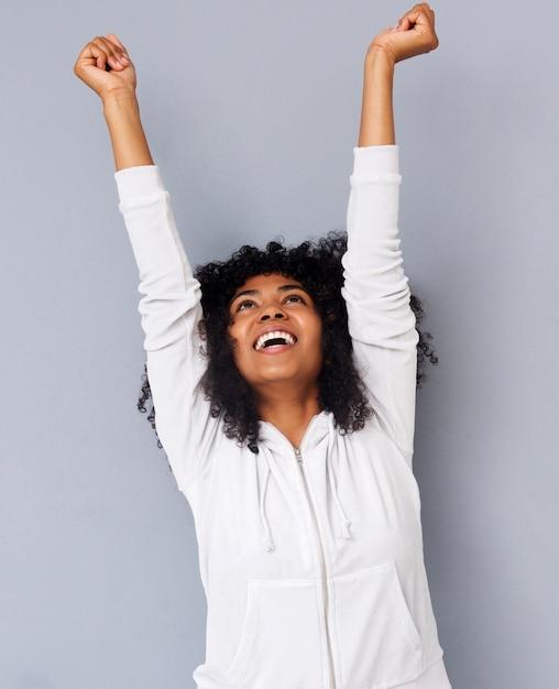 Joyeuse jeune femme afro-américaine rire avec les bras levés sur fond gris Photo Premium