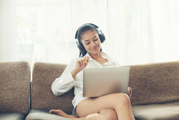 Joyeuse jeune femme écoutant de la musique à partir d'écouteurs tout en tenant un ordinateur portable Photo Premium