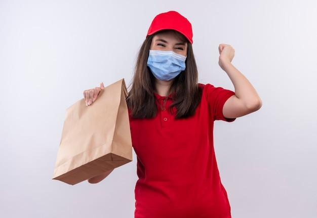 Joyeuse Jeune Femme De Livraison Portant Un T-shirt Rouge En Bonnet Rouge Tenant Un Paquet Sur Un Mur Blanc Isolé Photo gratuit