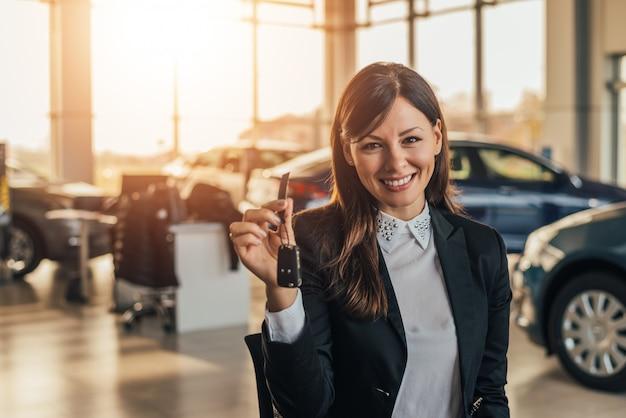 Joyeuse jeune femme montrant sa nouvelle clé de voiture chez un concessionnaire. Photo Premium