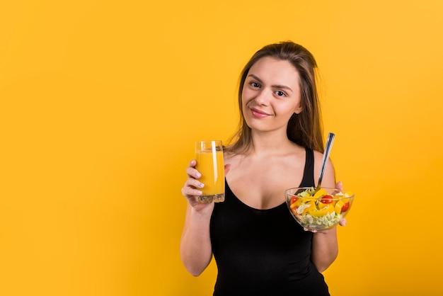 Joyeuse jeune femme avec un verre de jus de fruits et un bol de salade Photo gratuit