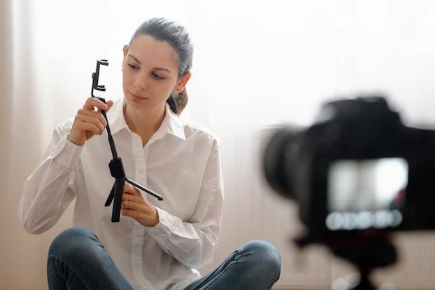 Joyeuse jeune fille en train d'enregistrer un épisode de blog vidéo sur les nouveaux appareils technologiques assis à la maison Photo Premium