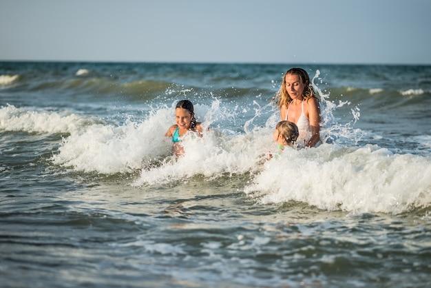 La Joyeuse Jeune Maman Nage Dans La Mer Avec Ses Charmantes Petites Filles Et Profite Du Week-end Tant Attendu Par Une Journée D'été Ensoleillée. Photo Premium