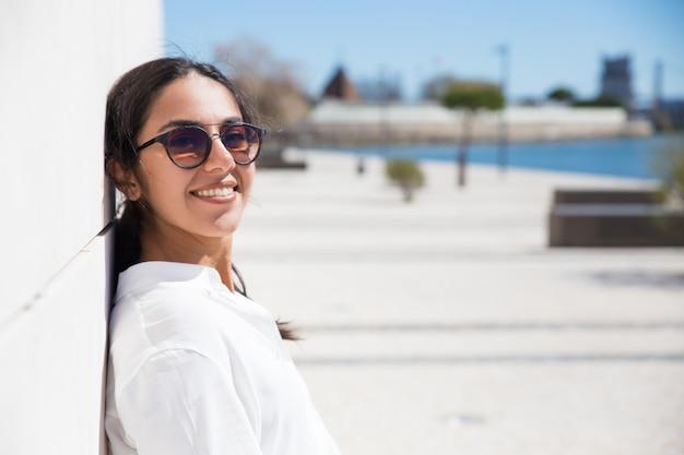 Joyeuse jeune touriste profitant de vacances au bord de mer Photo gratuit