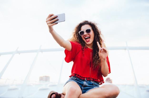 Joyeuse jolie fille aux cheveux bouclés prend un selfie sur téléphone mobile Photo gratuit