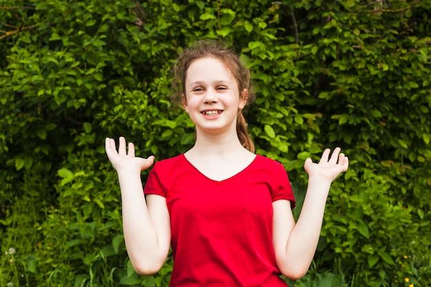 Joyeuse jolie fille debout dans le parc et gesticulant Photo gratuit