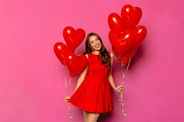 Joyeuse jolie fille avec long cheveux bouclés en robe rouge tenant des ballons à air chaud Photo gratuit
