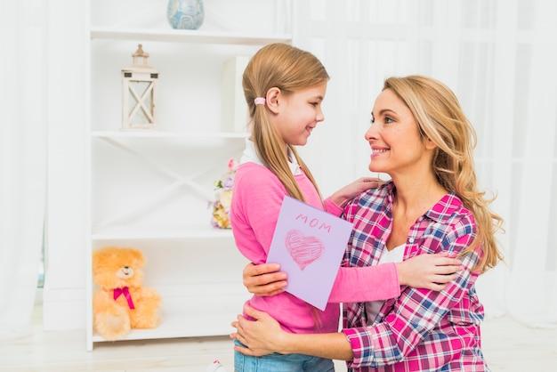 Joyeuse mère avec fille étreignant de carte de voeux Photo gratuit