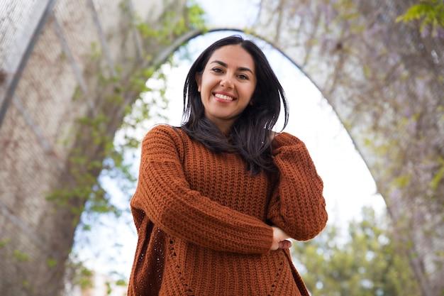 Joyeuse métisse fille en pull à pied dans le parc Photo gratuit