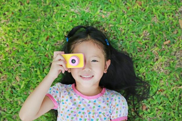 Joyeuse petite fille asiatique prend des photos avec l'appareil photo numérique coloré se trouvant sur la pelouse verte Photo Premium