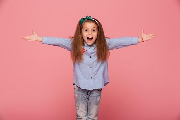 Joyeuse Petite Fille Dans Le Cerceau De Cheveux Posant Avec Les Mains Ouvertes étant Amical Et Accueillant Photo gratuit