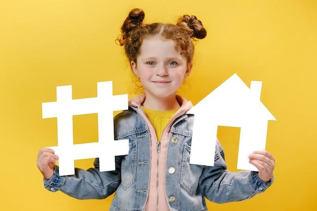 Joyeuse petite fille tenant un hashtag blanc et une maison sur fond jaune Photo Premium