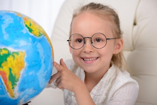 Joyeuse petite fille en vetu examinant le globe. Photo Premium