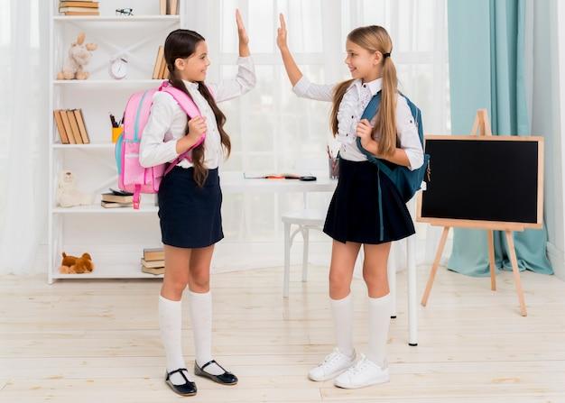 Joyeuses écolières donnant joyeusement cinq hautes Photo gratuit