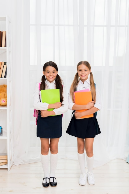 Joyeuses écolières multiethniques debout avec des cahiers Photo gratuit