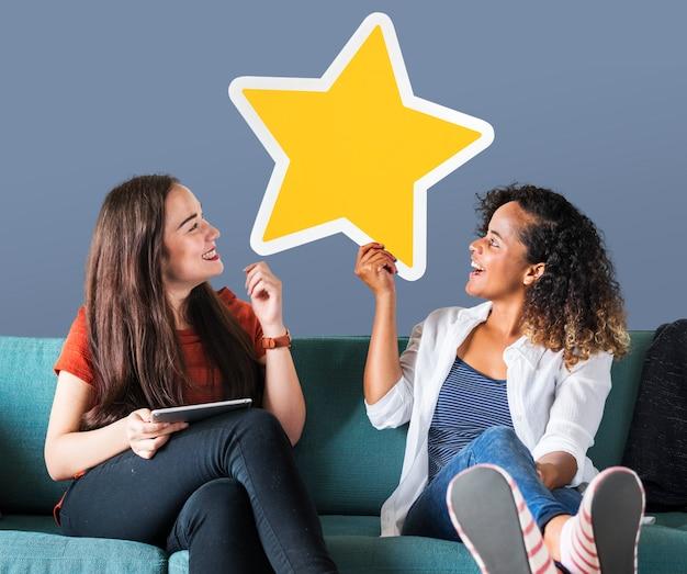 Joyeuses femmes tenant une icône étoile dorée Photo gratuit