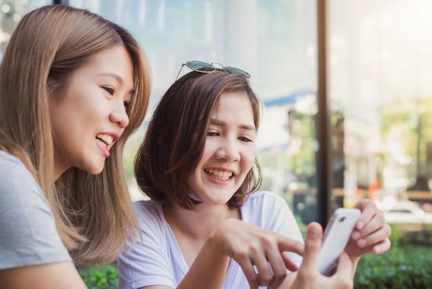 Joyeuses jeunes femmes asiatiques assis dans un café, boire du café avec des amis et parler ensemble Photo gratuit