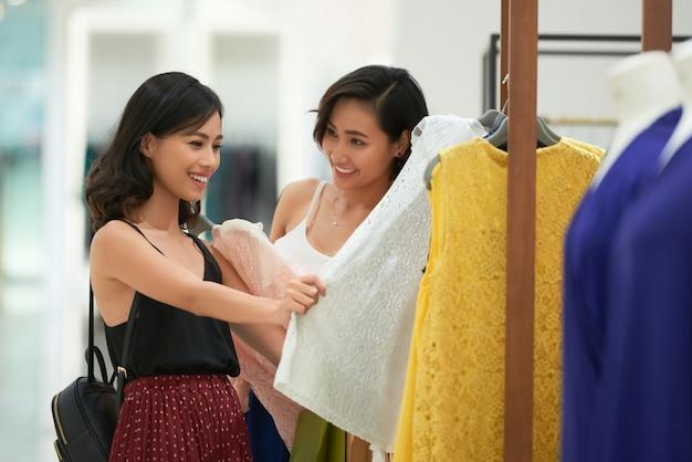 Joyeuses jeunes femmes faisant des emplettes pour des vêtements Photo gratuit