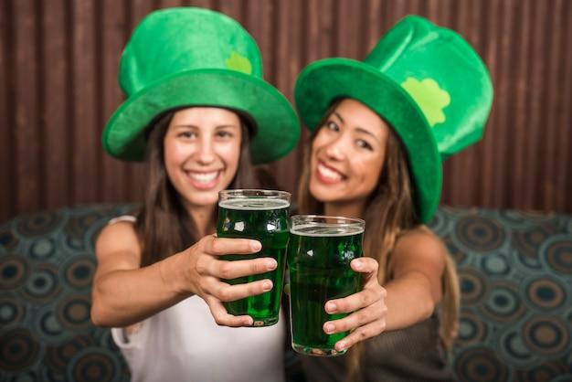 Joyeuses jeunes femmes montrant des verres de boisson sur le canapé Photo gratuit