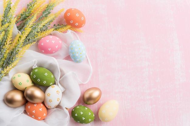 Joyeuses pâques! coloré des oeufs de pâques en nid avec fleur sur fond rose. Photo Premium