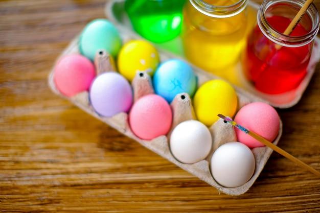 Joyeuses pâques avec des oeufs colorés dans le panier. décoration de table pour les vacances. vue de dessus. Photo Premium