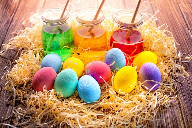 Joyeuses pâques avec des oeufs colorés en paille. décoration de table pour les vacances. vue de dessus. Photo Premium