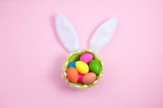 Joyeuses pâques avec des oreilles de lapin adorables sur un panier rempli d'oeufs de pâques sur fond rose Photo Premium