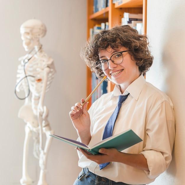 Joyeux adolescent avec un crayon et un cahier dans la bibliothèque Photo gratuit