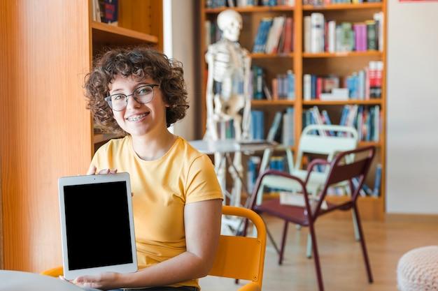 Joyeux adolescent montrant une tablette moderne Photo gratuit