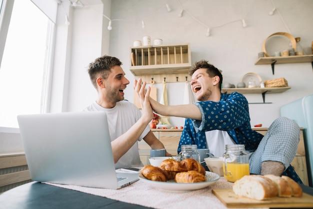 Joyeux amis applaudissements mains assis devant la table avec petit déjeuner et ordinateur portable Photo gratuit