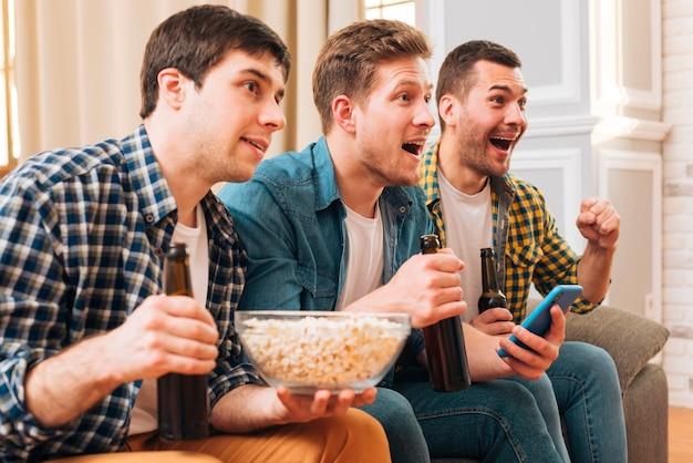 Joyeux amis excités tenant des bouteilles de bière à la main en regardant un match à la télévision Photo gratuit