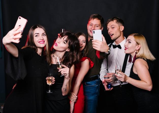 Joyeux amis faisant selfie avec du vin mousseux Photo gratuit
