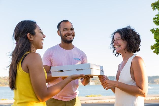 Joyeux amis heureux réunis en plein air pour pique-nique Photo gratuit