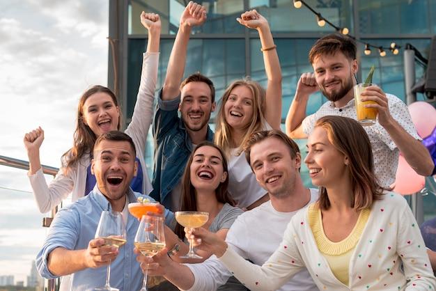 Joyeux amis posant lors d'une fête Photo gratuit