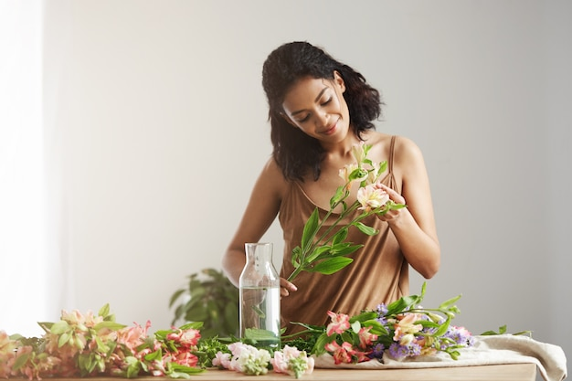 Joyeux Beau Fleuriste Africain Souriant Faisant Bouquet Au Lieu De Travail Sur Mur Blanc. Photo gratuit
