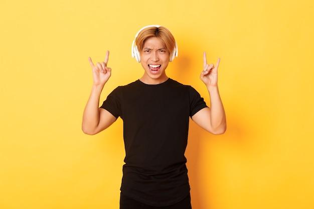 Joyeux Beau Mec Asiatique Appréciant L'écoute De La Musique Dans Les écouteurs, Montrant Le Geste Rock-n-roll, Debout Sur Le Mur Jaune Photo gratuit