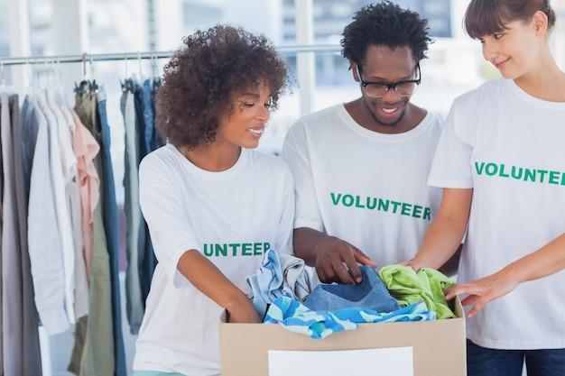Joyeux bénévoles prenant des vêtements dans une boîte de dons Photo Premium