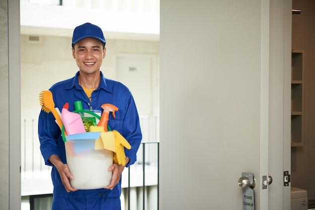 Joyeux Concierge Asiatique Mâle Marchant Dans La Chambre D'hôtel, Transportant Des Fournitures Dans Le Seau Photo gratuit