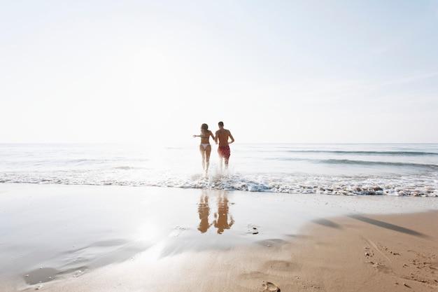 Joyeux couple en cours d'exécution sur le rivage Photo gratuit