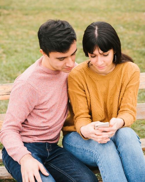 Joyeux couple dans le parc en regardant téléphone Photo gratuit