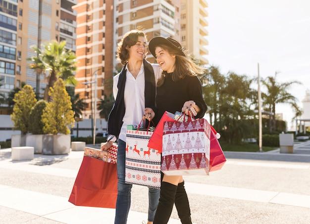 Joyeux couple marchant avec des sacs de noël Photo gratuit