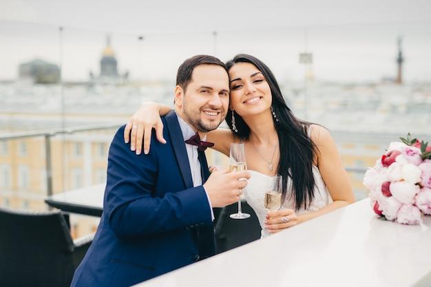 Joyeux couple marié s'embrasser, verres de champagne, bonne humeur après l'enregistrement de leur mariage Photo Premium