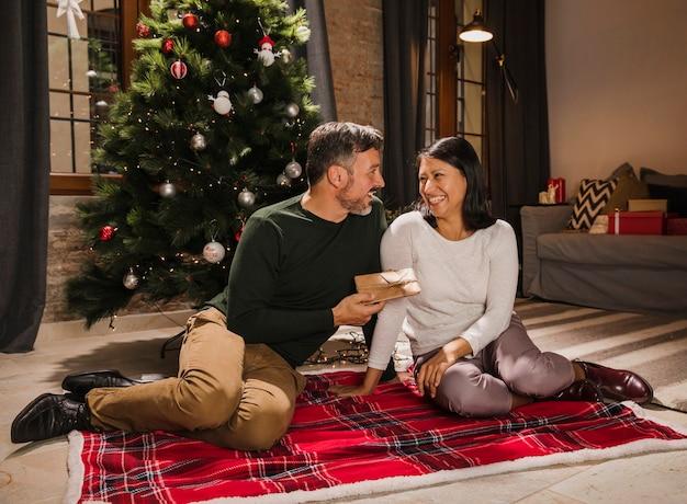 Joyeux Couple De Personnes âgées Souriant Et Offrant Des Cadeaux Les Uns Aux Autres Photo gratuit