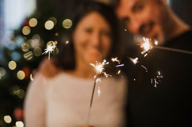 Joyeux couple de personnes âgées tenant un feu d'artifice Photo gratuit