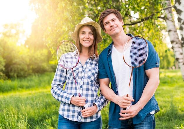 Joyeux couple avec des raquettes de badminton dans le parc Photo gratuit