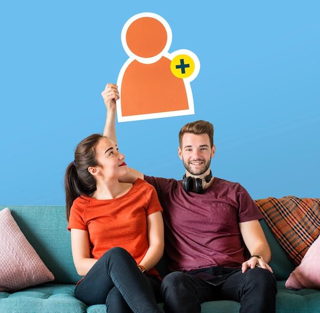 Joyeux couple tenant une icône de demande d'ami Photo gratuit