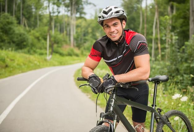 Joyeux cycliste mâle se penchant sur son vélo sur la route forestière Photo Premium