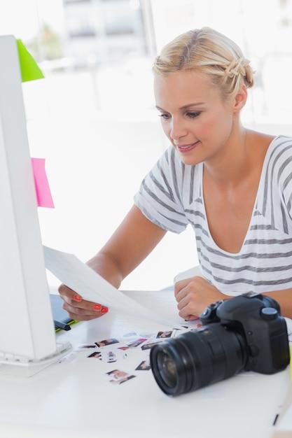 Joyeux éditeur de photos en regardant une feuille de contact Photo Premium