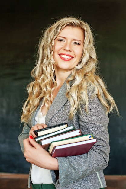 Joyeux élève avec des livres dans la classe. Photo Premium