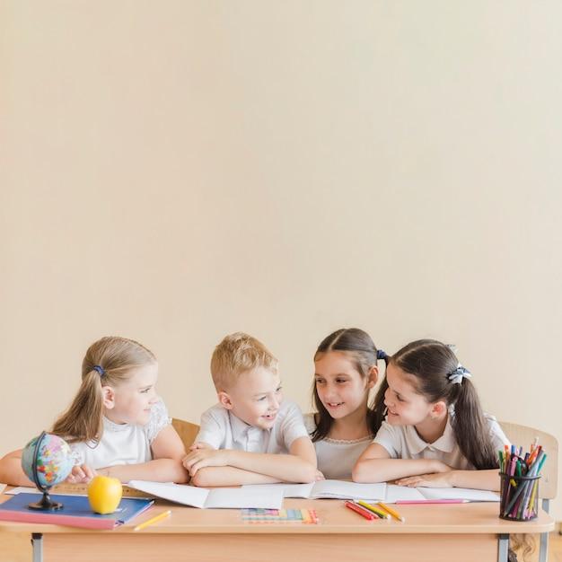 Joyeux élèves parlant pendant la leçon Photo gratuit